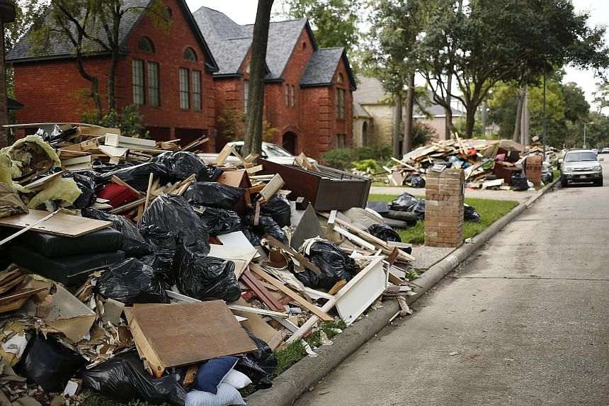 Piles of debris outside homes that were flooded after Hurricane Harvey hit the area of Spring in Texas. Harvey, which struck Texas last month, and Hurricane Irma, which hit Florida early this month, temporarily curbed economic activity but rebuilding