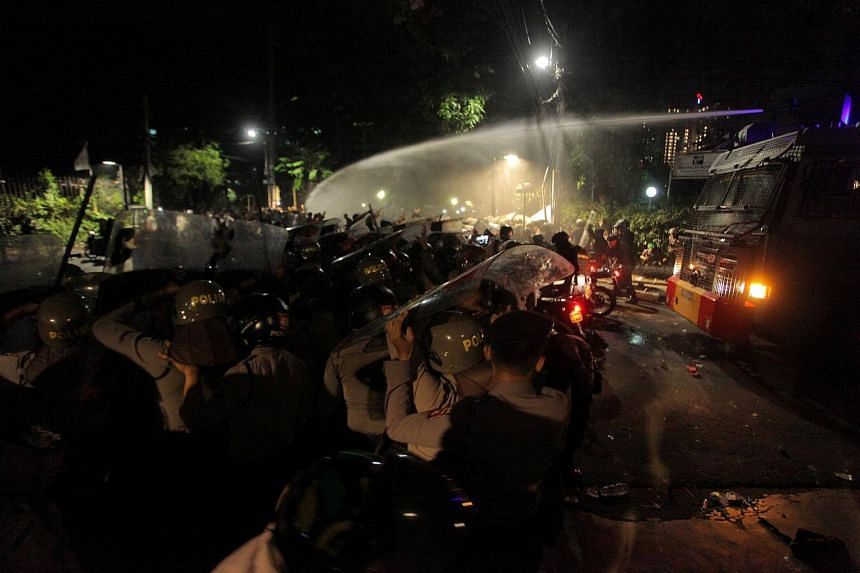 Police use a water cannon to disperse a crowd gathered outside the Indonesian Legal Aid Foundation during an anti-communist protest in Jakarta, Indonesia, on Sept 18, 2017.
