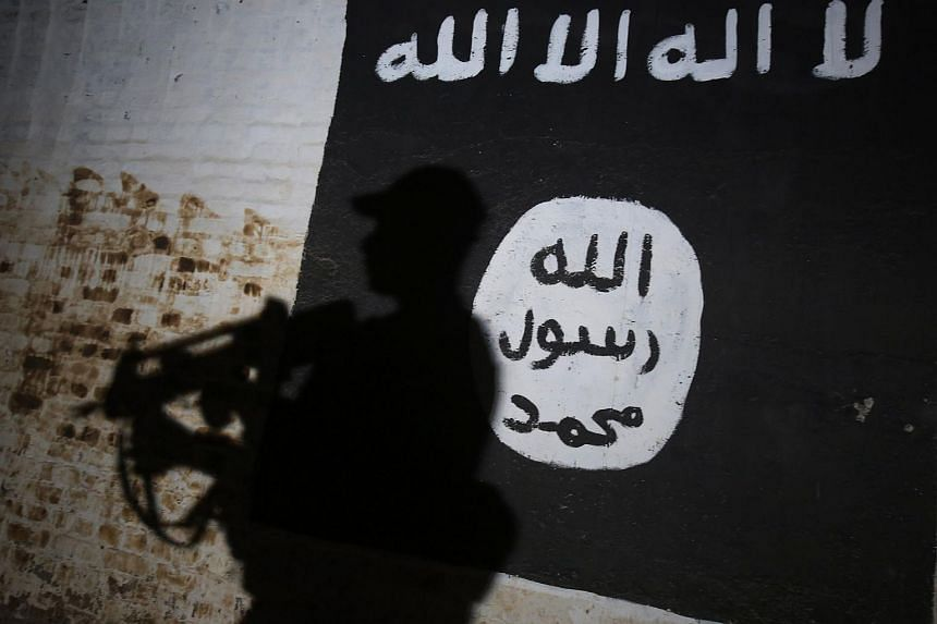 A member of the Iraqi forces walks past a mural bearing the logo of the Islamic State of Iraq and Syria  in a tunnel that was used as a training centre by the jihadists, on March 1, 2017.