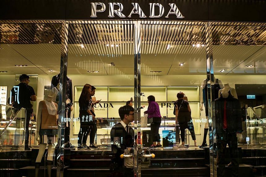 Customers browse  merchandise inside a Prada SpA luxury fashion store on Canton Road in Hong Kong, China.