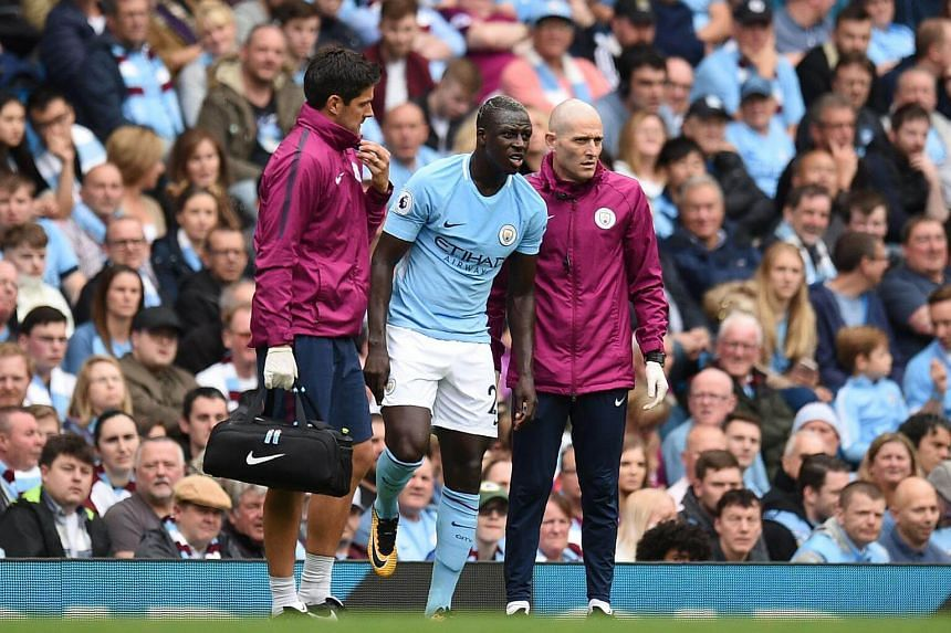 Manchester City's French defender Benjamin Mendy is helped by medics during the English Premier League football match between Manchester City and Crystal Palace at the Etihad Stadium in Manchester, on Sept 23, 2017.