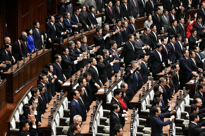 Lawmakers raise their hands shouting 'banzai!' (Hurrah!) after the dissolution of the Lower House of the Parliament in Tokyo, on Sept 28, 2017.