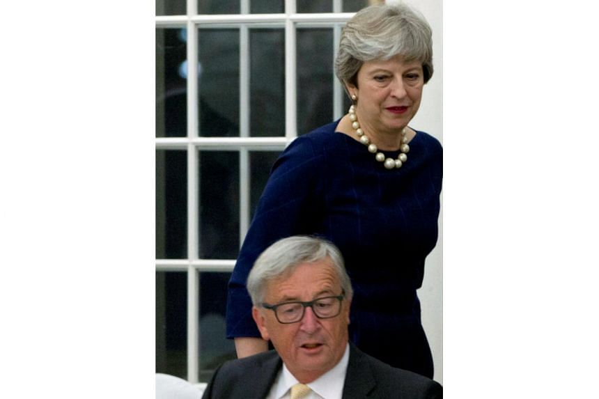 Britain's Prime Minister Theresa May walks past European Commission President Jean-Claude Juncker during a dinner in Tallinn ahead of an informal European Union leaders summit, Estonia on Sept 28, 2017.  She had hoped to harness renewed goodwill over