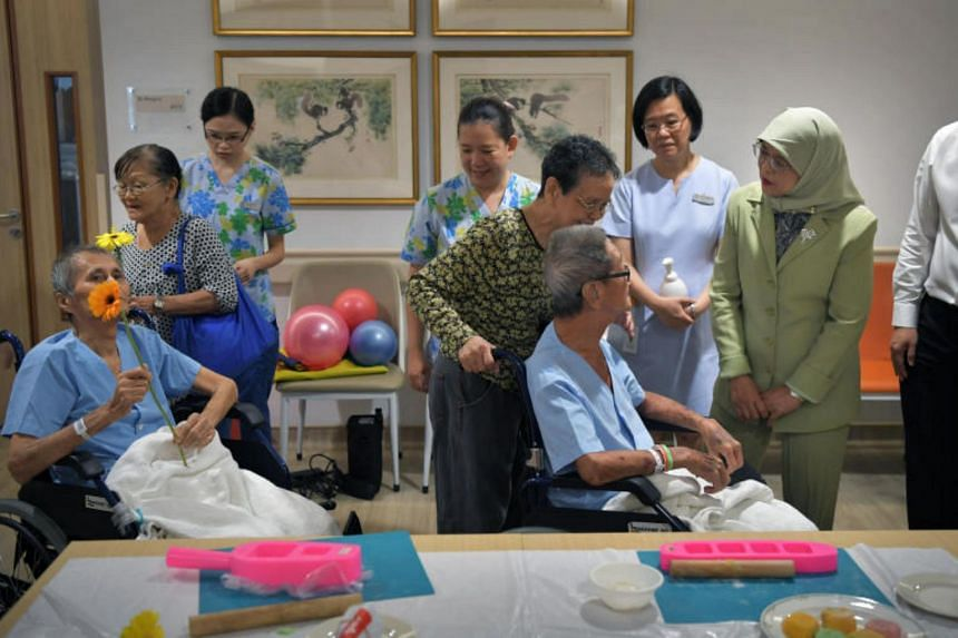 President Halimah Yacob speaks with a patient during her visit to the Assisi Hospice on Sept 29, 2017.