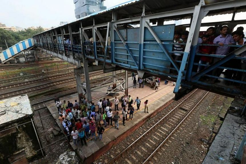 Commuters walk on the foot overbridge at Elphinston Road railway station in Mumbai, India on Sept 29, 2017.