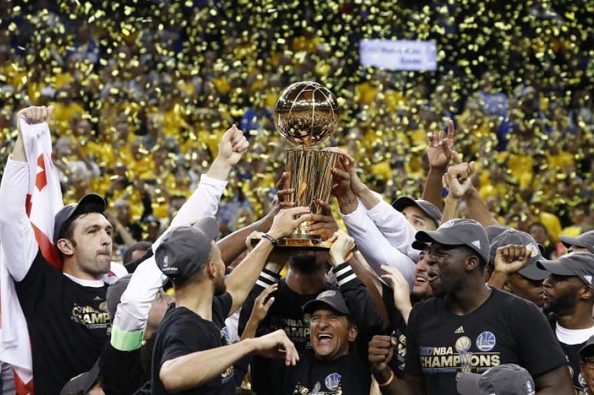 Golden State Warriors celebrate with the Larry O'Brien NBA Championship Trophy, after winning the NBA Finals against the Cleveland Cavaliers in Game Five at Oracle Arena in Oakland, California, on June 12, 2017.