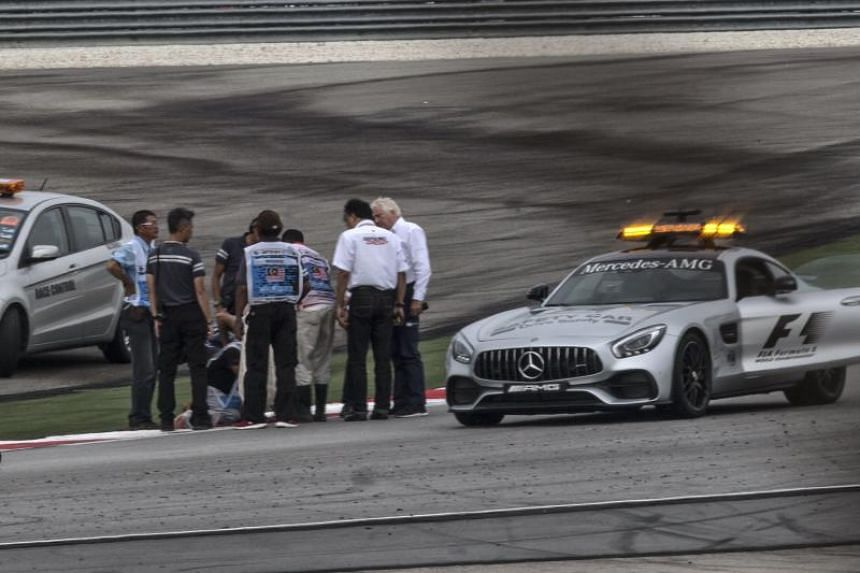 FIA (International Automobile Federation) officials inspect the Sepang International Circuit track after French Formula One driver Romain Grosjean of Haas crashed during the second practice session on Sept 29, 2017. The Malaysian Grand Prix will take