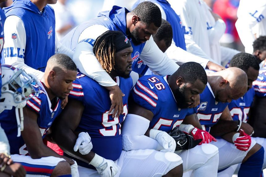 Buffalo Bills players kneel during the American national anthem before an NFL game against the Denver Broncos.