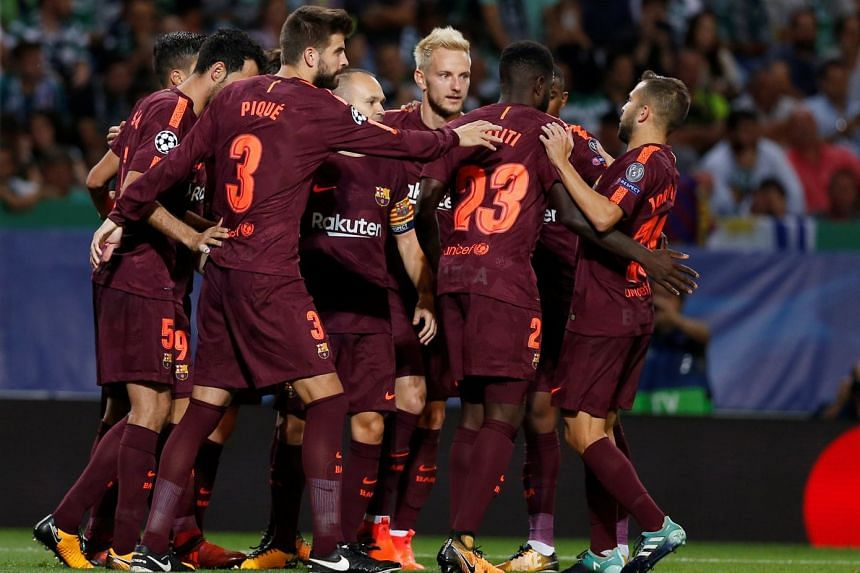 Barcelona's Andres Iniesta, Gerard Pique and teammates celebrate their first goal scored by Sporting's Sebastian Coates with an own goal during the Sporting CP vs FC Barcelona Champions League match, on Sept 27, 2017.