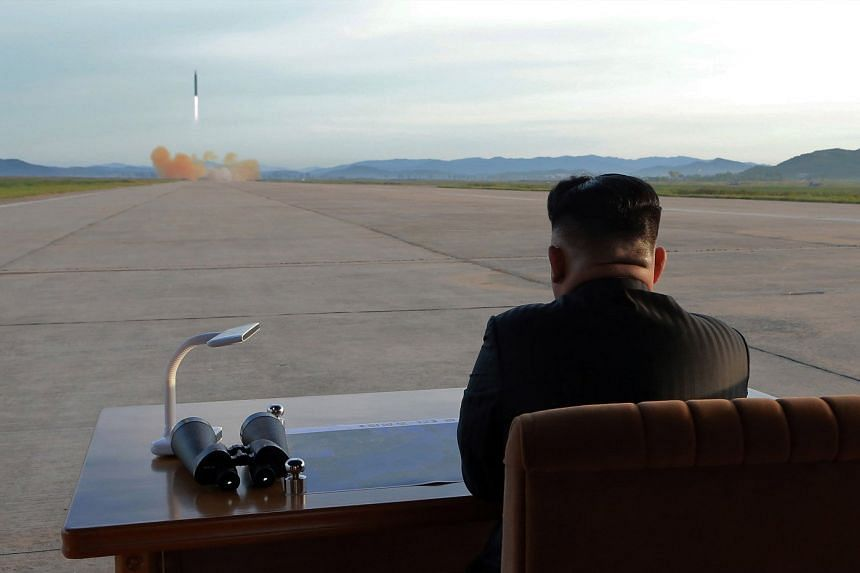 Kim Jong Un guiding the launch of the medium-to-long range strategic ballistic rocket Hwasong-12 at an unspecified location.