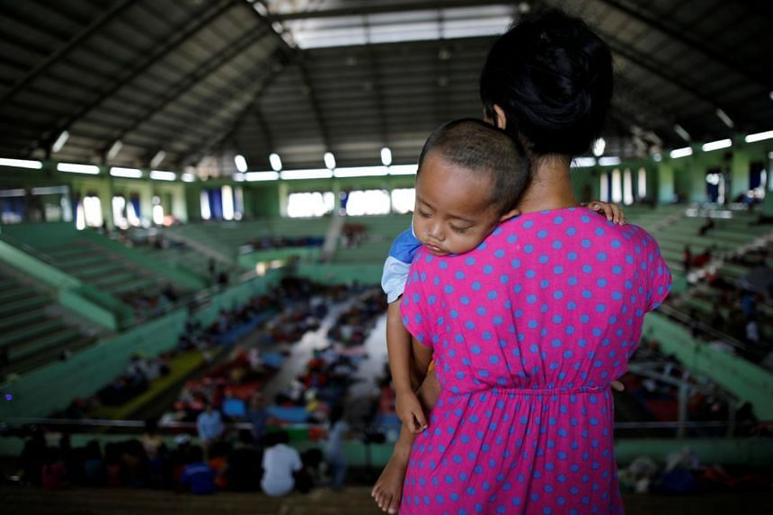 A woman holds her child inside a temporary evacuation center for people living near Mount Agung in Bali, Indonesia, on Sept 28, 2017.