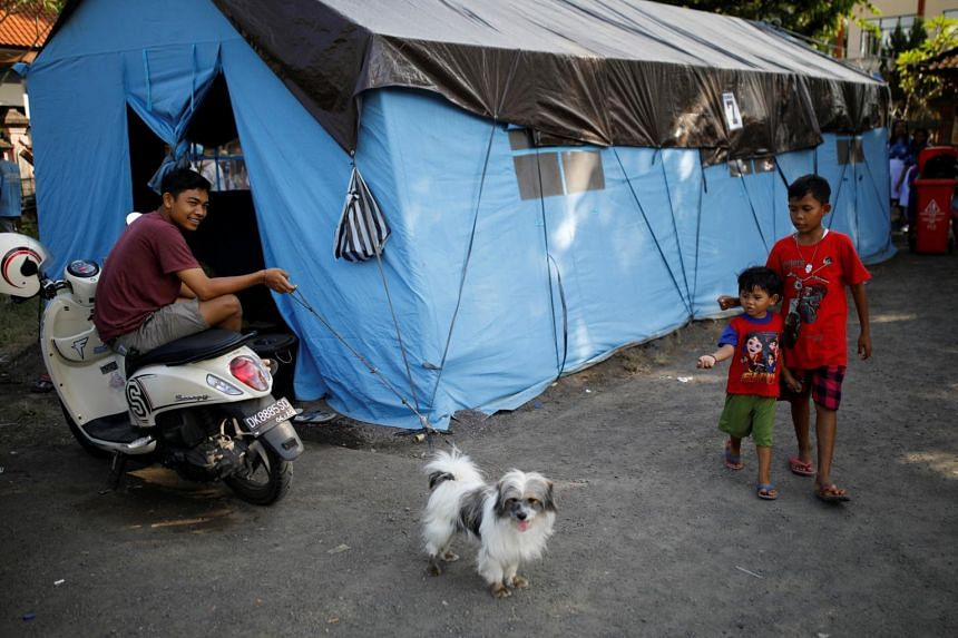 A man holds his dog on a leash outside a tent at a temporary evacuation center for people living near Mount Agung in Bali, Indonesia, on Sept 28, 2017.