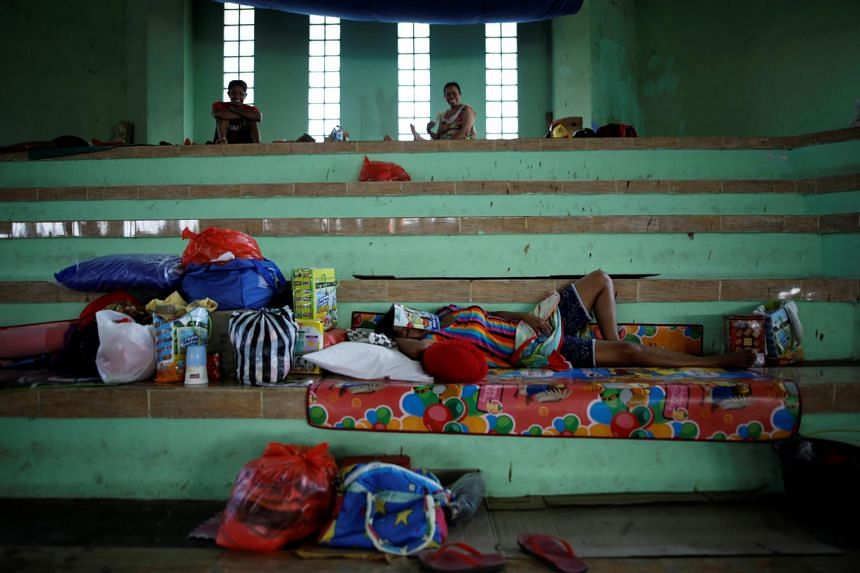 A woman sleeps inside a temporary evacuation center for people living near Mount Agung in Bali, Indonesia, on Sept 28, 2017.