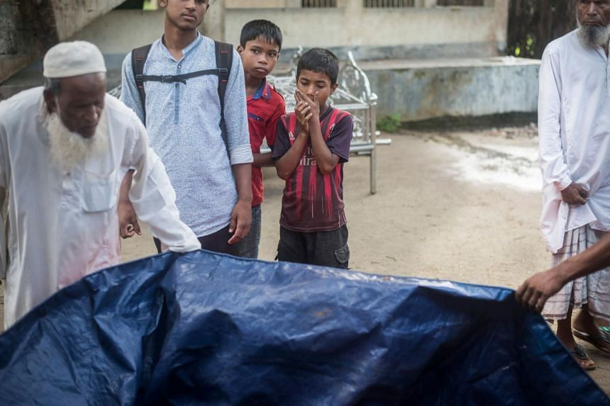 People gather around the bodies of Rohingya Muslim refugees at a school near Inani beach, Cox's Bazar, on Sept 29, 2017.