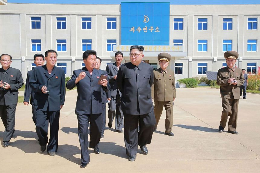 North Korean leader Kim Jong-Un with officials visiting a fruit farm research institute