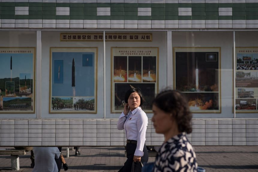 People walk past images showing North Korean missile test launches outside the central railway station in Pyongyang.
