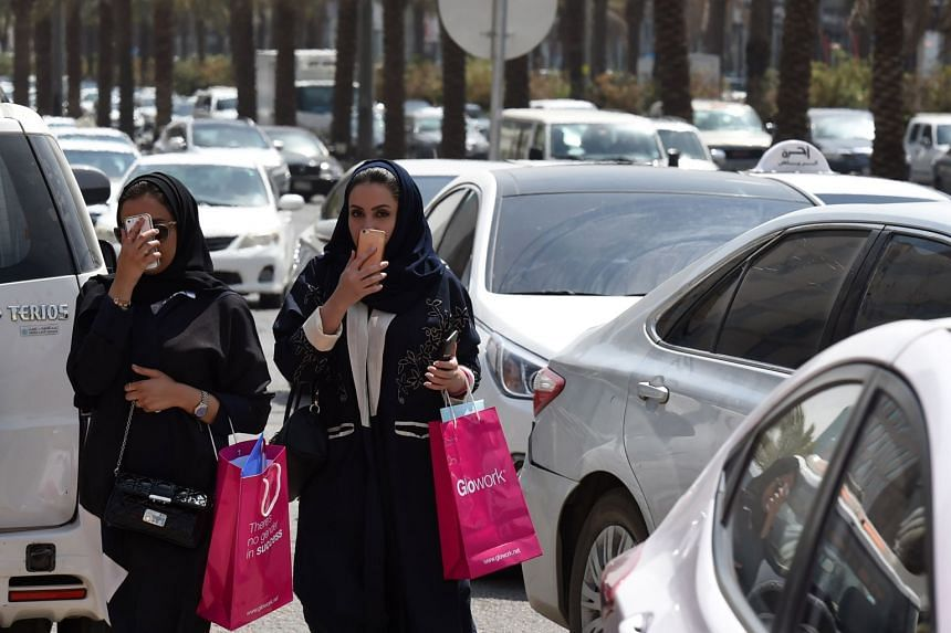 Saudi women walk amid vehicles in a street in the Saudi capital Riyadh, on Sept 28, 2017.