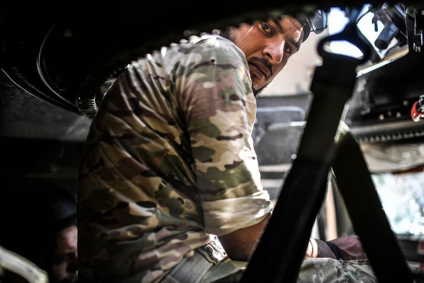 A member of the Syrian Democratic Forces  sits inside a humvee during a battle against ISIS militants to retake the central hospital of Raqa, Sept 28, 2017.