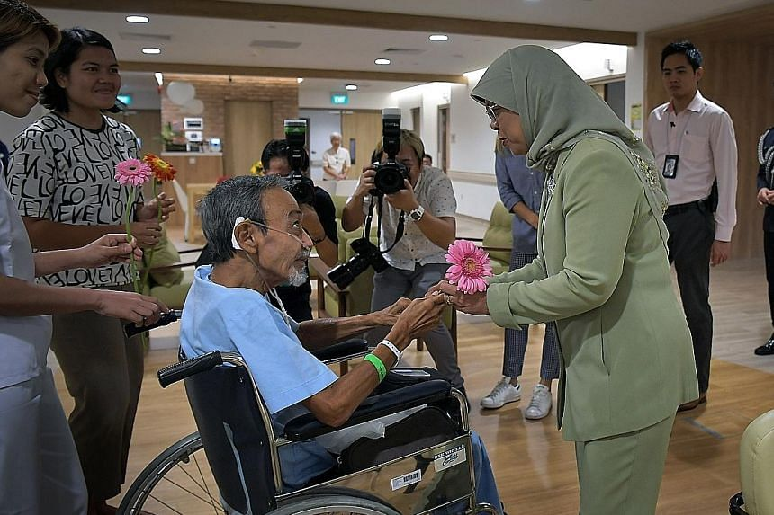 Freelance photographer Alan Lee, 69, who has an exhibition of photos showcasing the everyday lives of his fellow patients at Assisi Hospice, meeting President Halimah Yacob yesterday when she visited the facility in Thomson Road. In a Facebook post,
