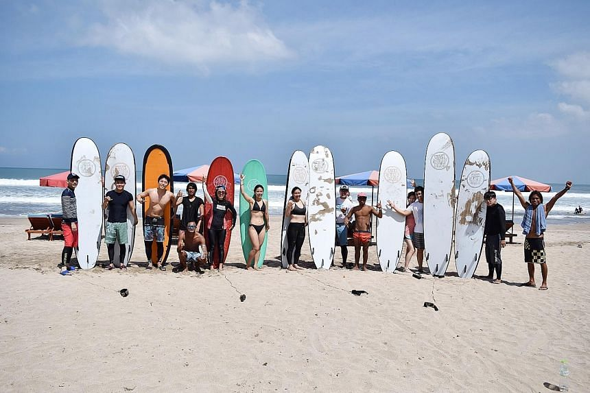South Korean President Moon Jae In greeting other visitors to Odaesan while visiting the mountain during his summer vacation in July. Above: Ms Gwen Chang (fourth from right), seen here beside her husband, went surfing in Bali over the Chuseok holida