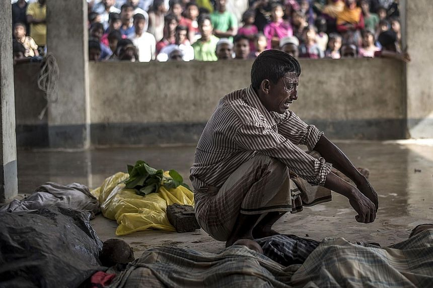A Rohingya refugee mourning beside the bodies of his three children who drowned when a boat carrying Rohingya families capsized off the coast of Bangladesh on Thursday.