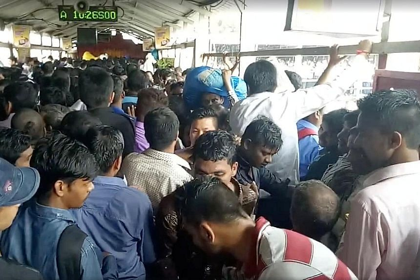 Above: A man injured in the crush being taken to hospitalLeft: The crowd of commuters on the bridge at the Elphinstone railway station in Mumbai yesterday, in a picture taken before the stampede occurred.