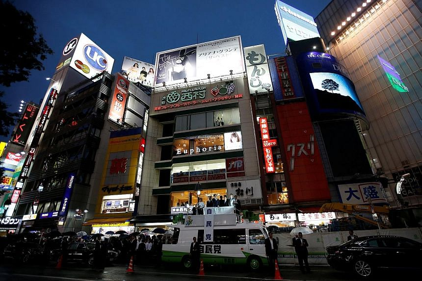 Japanese Prime Minister Shinzo Abe, who is also leader of the ruling Liberal Democratic Party, delivering a speech on top of a campaign van in Tokyo's Shibuya district yesterday. His trademark Abenomics policy has helped Japan stave off deflation but