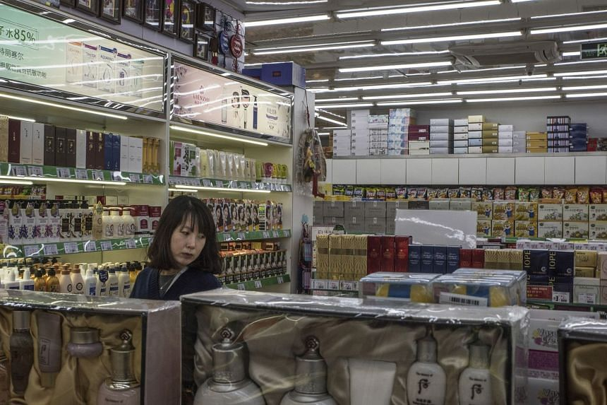 A customer looks at cosmetics at a Korean supermarket in Beijing, Sept 28, 2017.