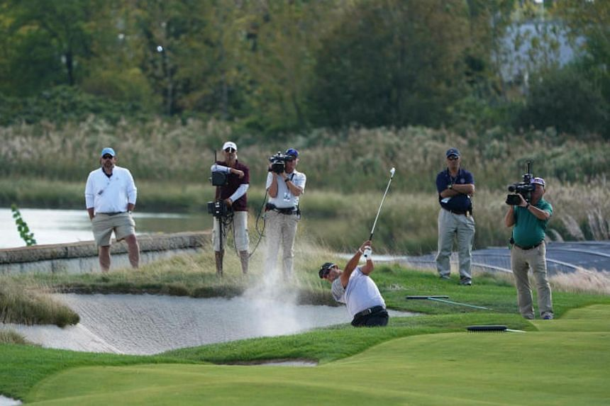 Hideki Matsuyama of the International team hitting from the sand on the 14th hole during the second round four-ball matches of The President's Cup golf tournament at Liberty National Golf Course on Sept 29, 2017.