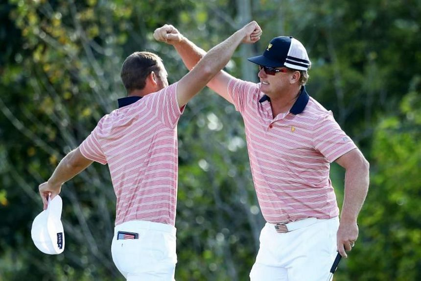 Kevin Chappell and Charlie Hoffman of the US team celebrate on the 13th green after defeating the International team's Anirban Lahiri of India and Charl Schwartzel of South Africa 6&5 in Friday's four-ball match.