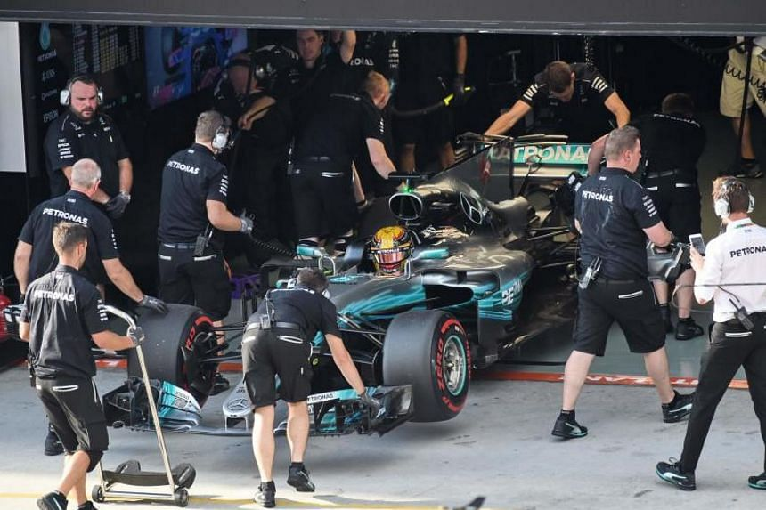 Crew team pushes Mercedes' British driver Lewis Hamilton to the garage during the Formula One Malaysia Grand Prix at the Sepang circuit near Kuala Lumpur on Sept 30, 2017.