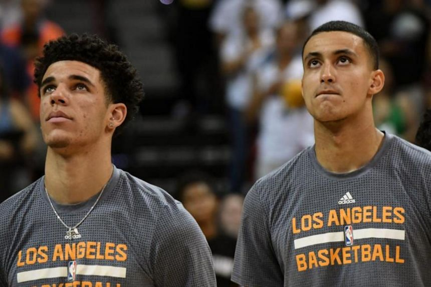 Lonzo Ball (left) #2 and Kyle Kuzma #0 of the Los Angeles Lakers stand on the court as the American national anthem is performed before the championship game of the 2017 Summer League against the Portland Trail Blazers at the Thomas & Mack Center on