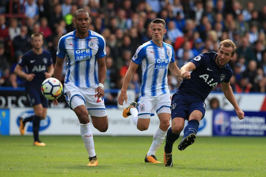 Tottenham Hotspur's English striker Harry Kane (right) shoots to score their third goal, his second, during the English Premier League football match against Huddersfield Town at the John Smith's Stadium on Sept 30, 2017.
