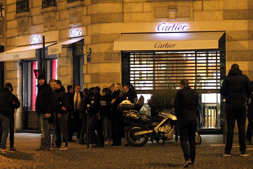Police officers in front of a Cartier jewellery store on the Champs-Elysees avenue in Paris, after a robbery took place on Nov 25, 2014.