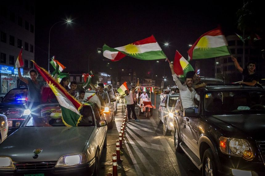 People celebrate with Kurdish flags on the streets of Irbil, Iraq, after the results of the referendum.
