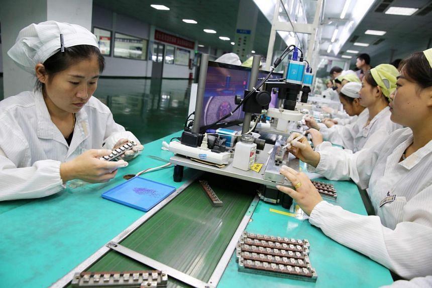 Chinese employees working on a micro special motor production line at a factory in Huaibei in China's eastern Anhui province on Sept 21, 2017.