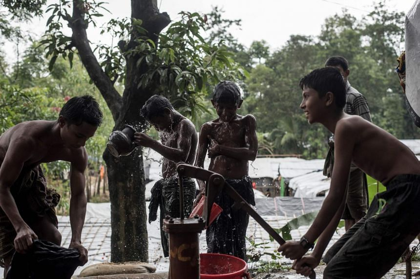 Rohingya Muslim refugees shower using a water pump at the Kutupalong refugee camp in Ukhia, Cox's Bazar on Sept 28, 2017.