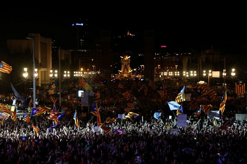 People wave Esteladas (Catalan separatist flags) as they attend a closing rally in favour of the banned Oct 1 independence referendum in Barcelona, Spain, on Sept 29, 2017.