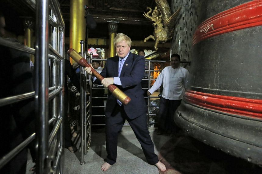 Boris Johnson attempts to ring a bell as he visits the Shwedagon Pagoda in Yangon.