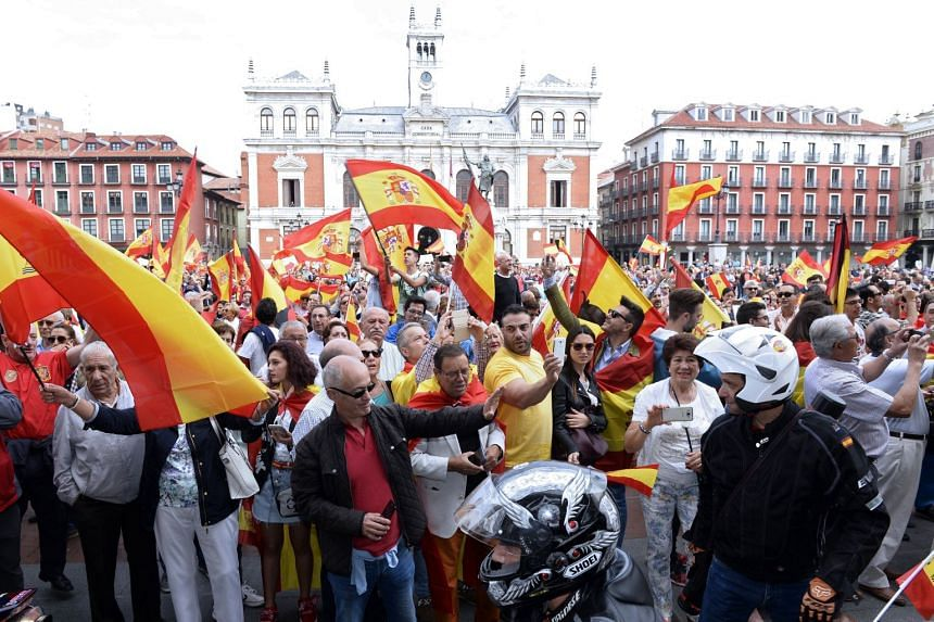 People wave Spanish national flags during a protest in support of Spain's unity at the main square of Valladolid.