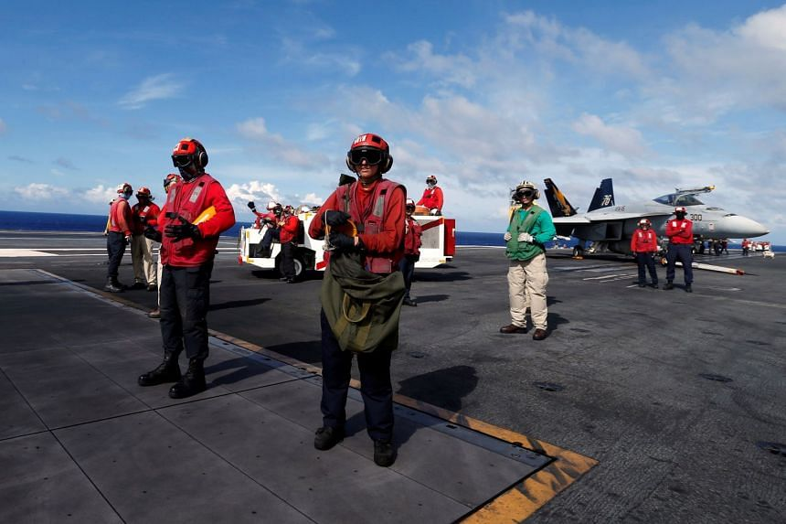 Crew members are seen on duty, on the deck of the USS Ronald Reagan, Sept 30, 2017.