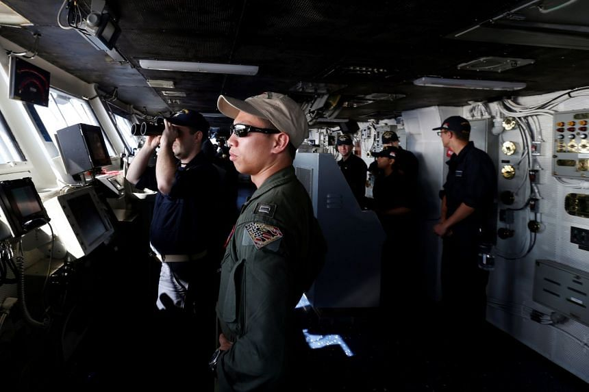 Crew members are seen on duty, on the bridge of the USS Ronald Reagan, Sept 30, 2017.