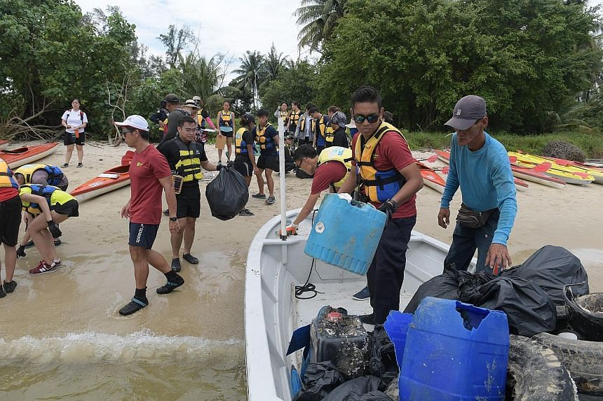 Some of the 100 or so volunteers who spent three hours collecting trash between Sembawang Beach and Seletar Island yesterday. The Clean-Up on Kayak event was organised by the MPA.