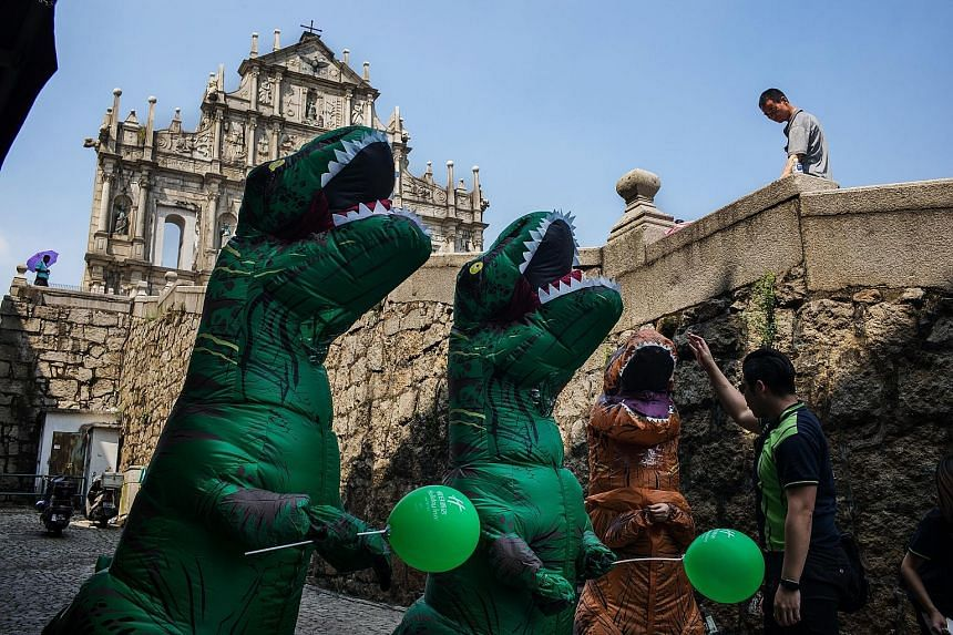 A man interacts with workers dressed in dinosaur costumes at the ruins of St Paul's Cathedral in Macau on Wednesday. Around 710 million Chinese will make trips within the country during the Golden Week holiday.