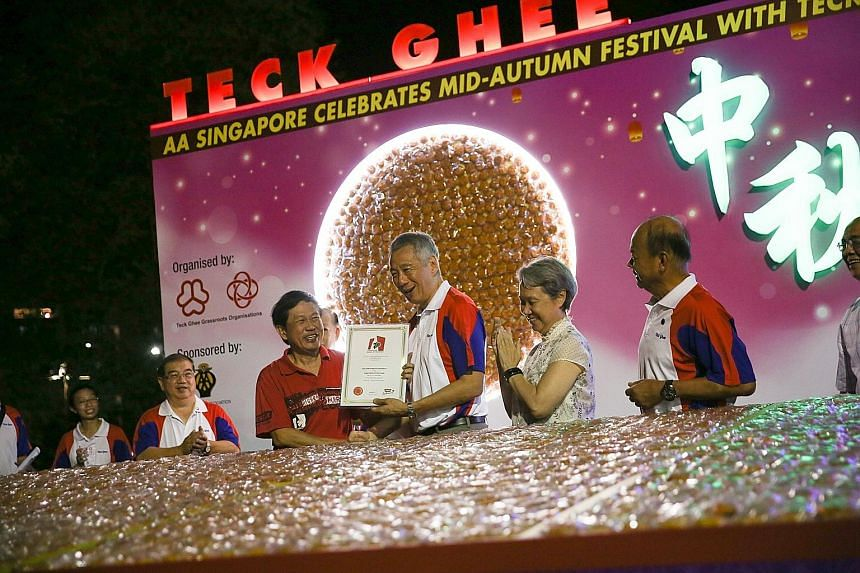 Prime Minister Lee Hsien Loong, accompanied by his wife, Mrs Lee, being presented with a Singapore Book of Records certificate for the most number of mooncakes displayed, at Teck Ghee Lantern Night 2017 yesterday. A total of 40,100 miniature mooncake
