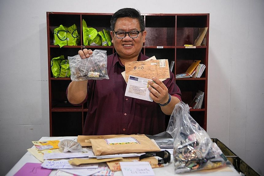 Mr James Cheong showing some of the items that ended up at SingPost's Returned Letters Unit last Wednesday, such as letters addressed to God and North Korean leader Kim Jong Un, as well as broken glass bottles.