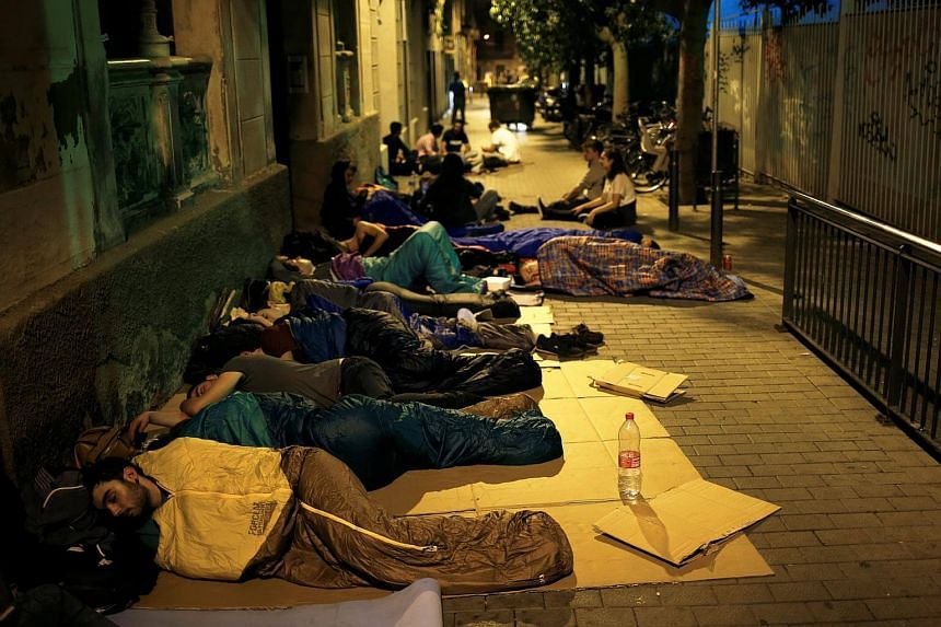 Parents and citizens camp out at the entrance of the occupied Reina Violant elementary school, one of the designated polling stations, in Barcelona, on Oct 1, 2017.