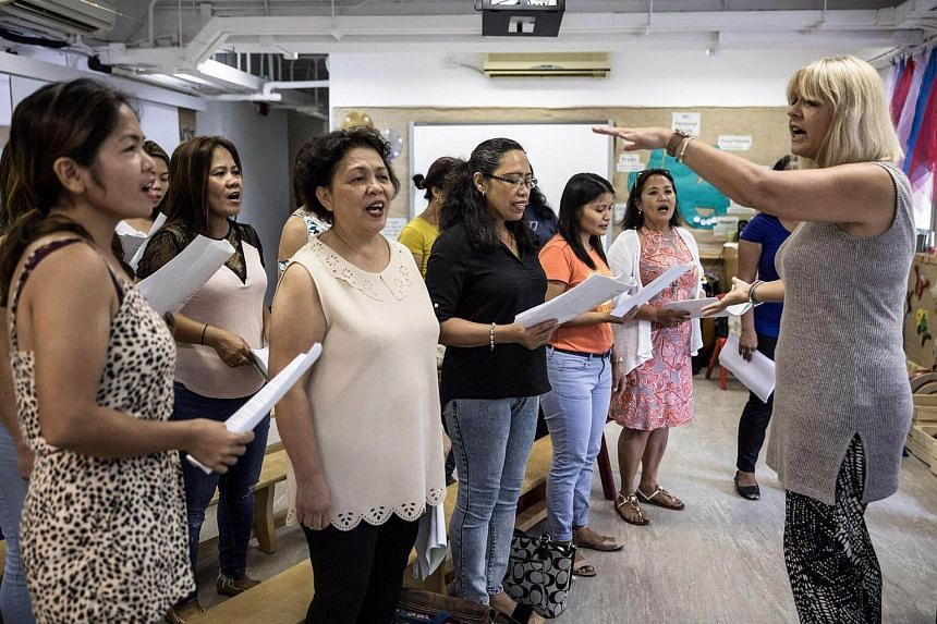 Unsung Heroes choir founder Jane Englemann leads her group of Filipina domestic workers during a practice session inside a kindergarten school's classroom in Hong Kong on Sept 3, 2017.