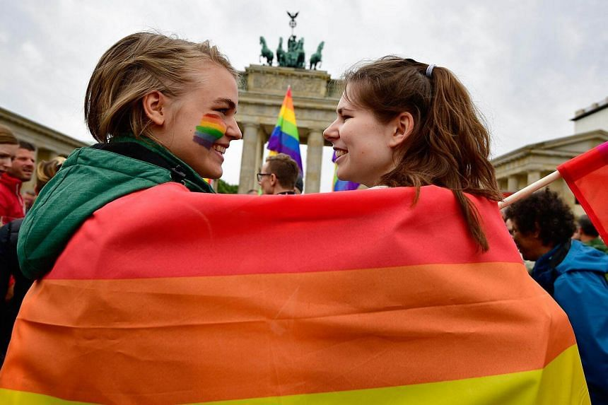 Two young women wrapped into a rainbow flag as they attend a rally of gays and lesbians in front of the Brandenburg Gate in Berlin, on June 30, 2017.