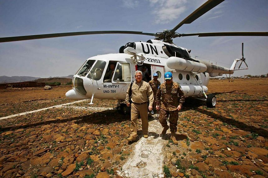 Steven Koutsis (left), the United States' top envoy in Sudan, disembarking from a United Nation's humanitarian air operations (UNHAS) helicopter after landing in the war-torn town of Golo in central Darfur.